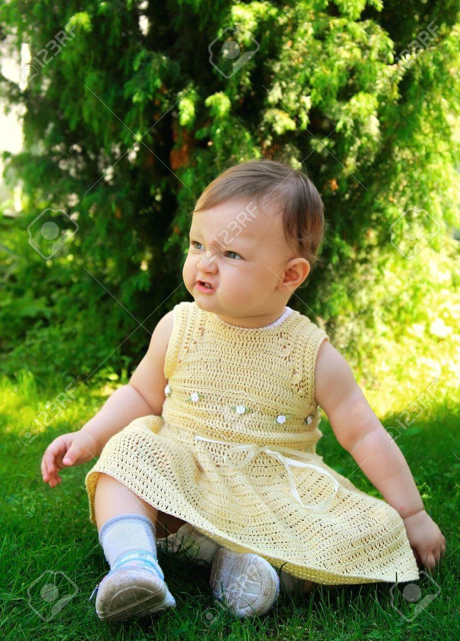 Fun baby girl in dress sitting on green grass on summer trees background Stock Photo - 14122955