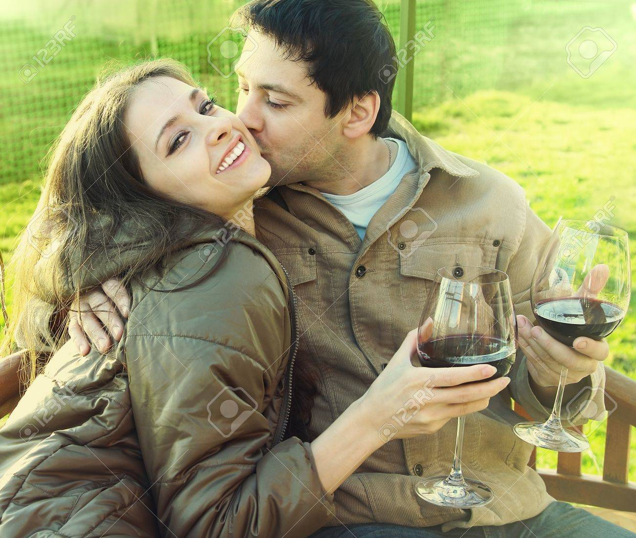 Happy couple drinking red wine outdoor  Man kissing laughing beautiful girl with long hair  She is looking in camera  Closeup bright portrait of happiness and leisure with drink in sunny autumn day Stock Photo - 15720962