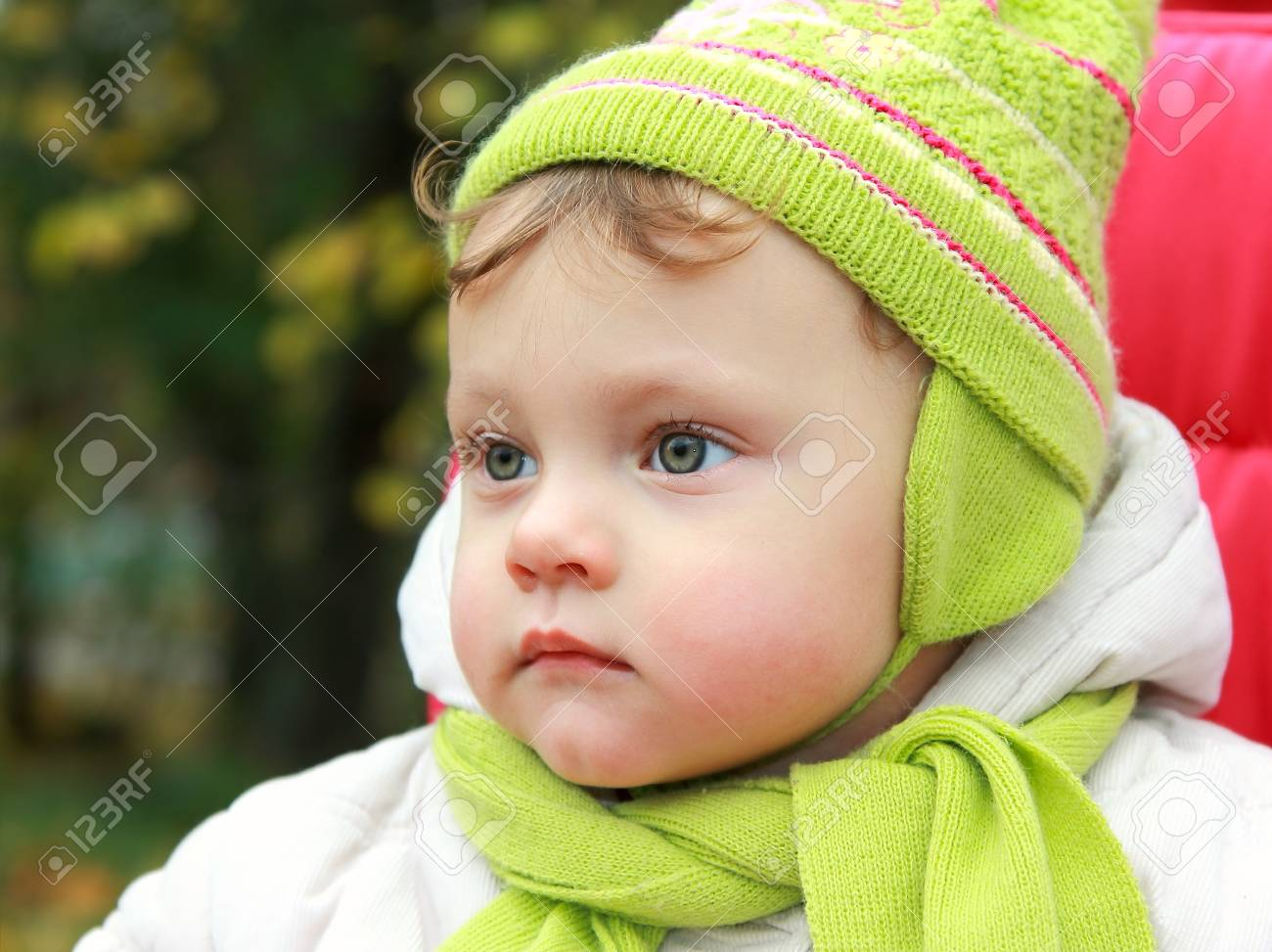 Closeup portrait of serious baby looking in hat and scarf on autumn background Stock Photo - 15866162