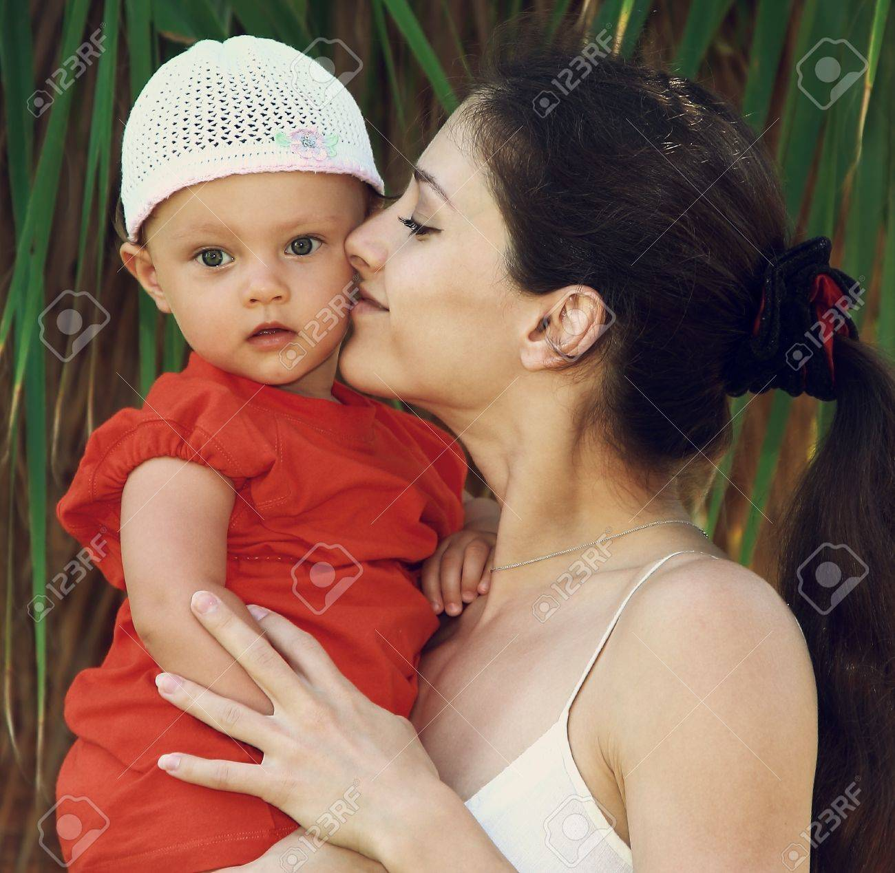 Mother kissing baby girl in hat holding on hands outdoors green trees background Stock Photo - 17057134
