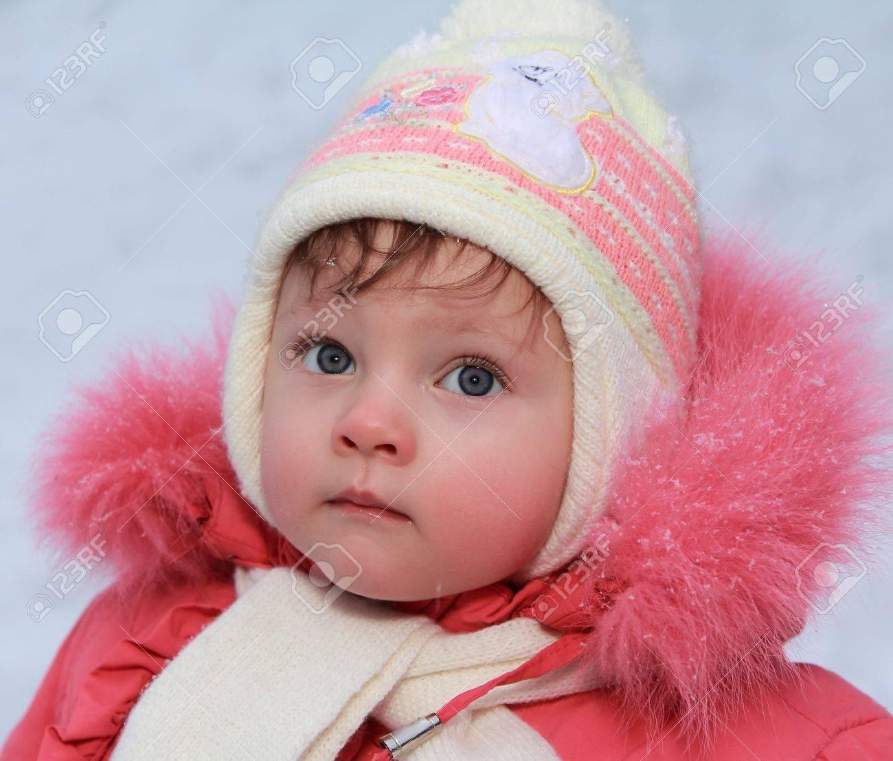 5ba912f43 Winter Baby Girl In Hat Looking Blue Fun Eyes In Red Coat Closeup ...