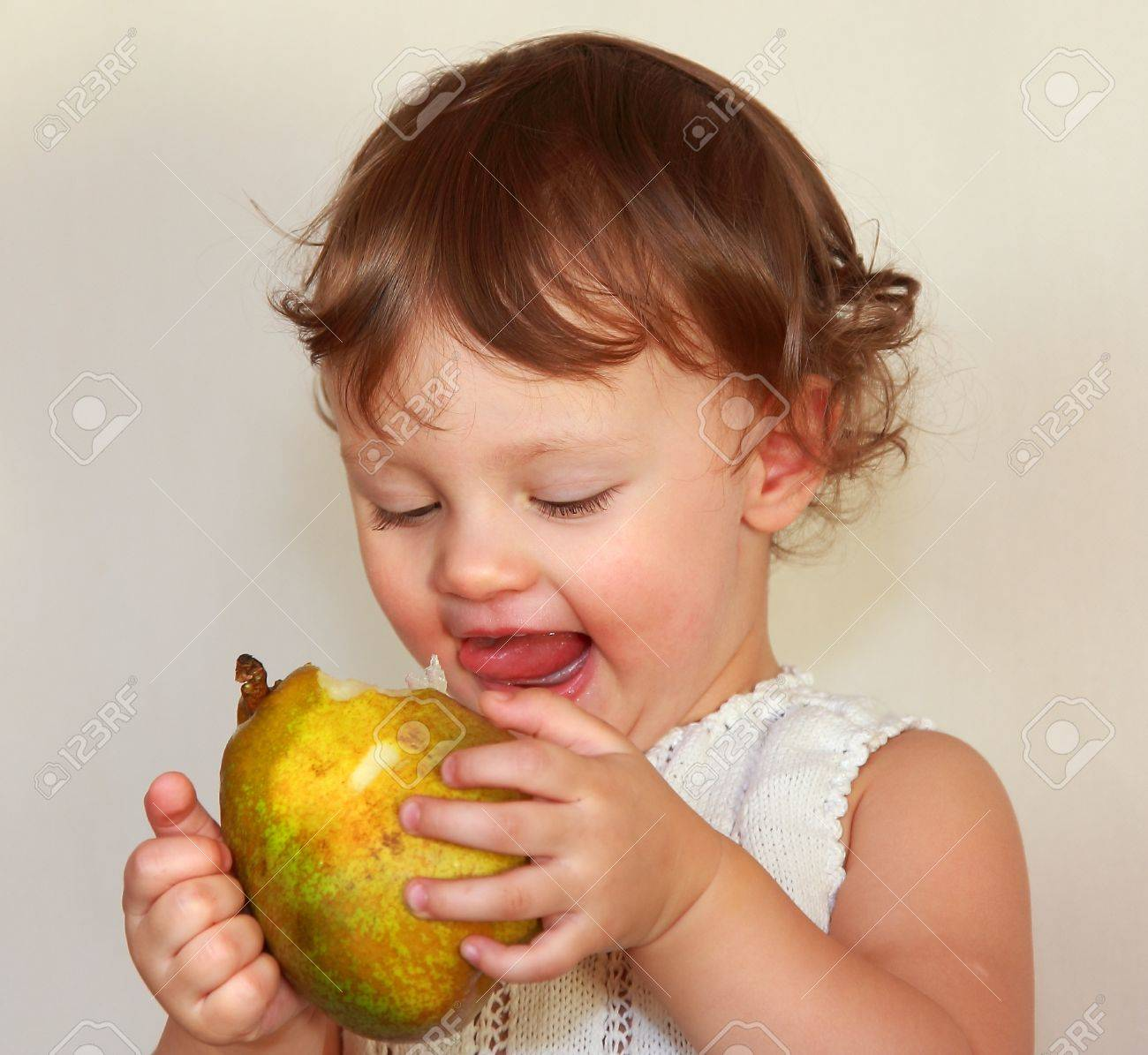 Happy baby eating big pear with joy face  Closeup portrait Stock Photo - 17536889
