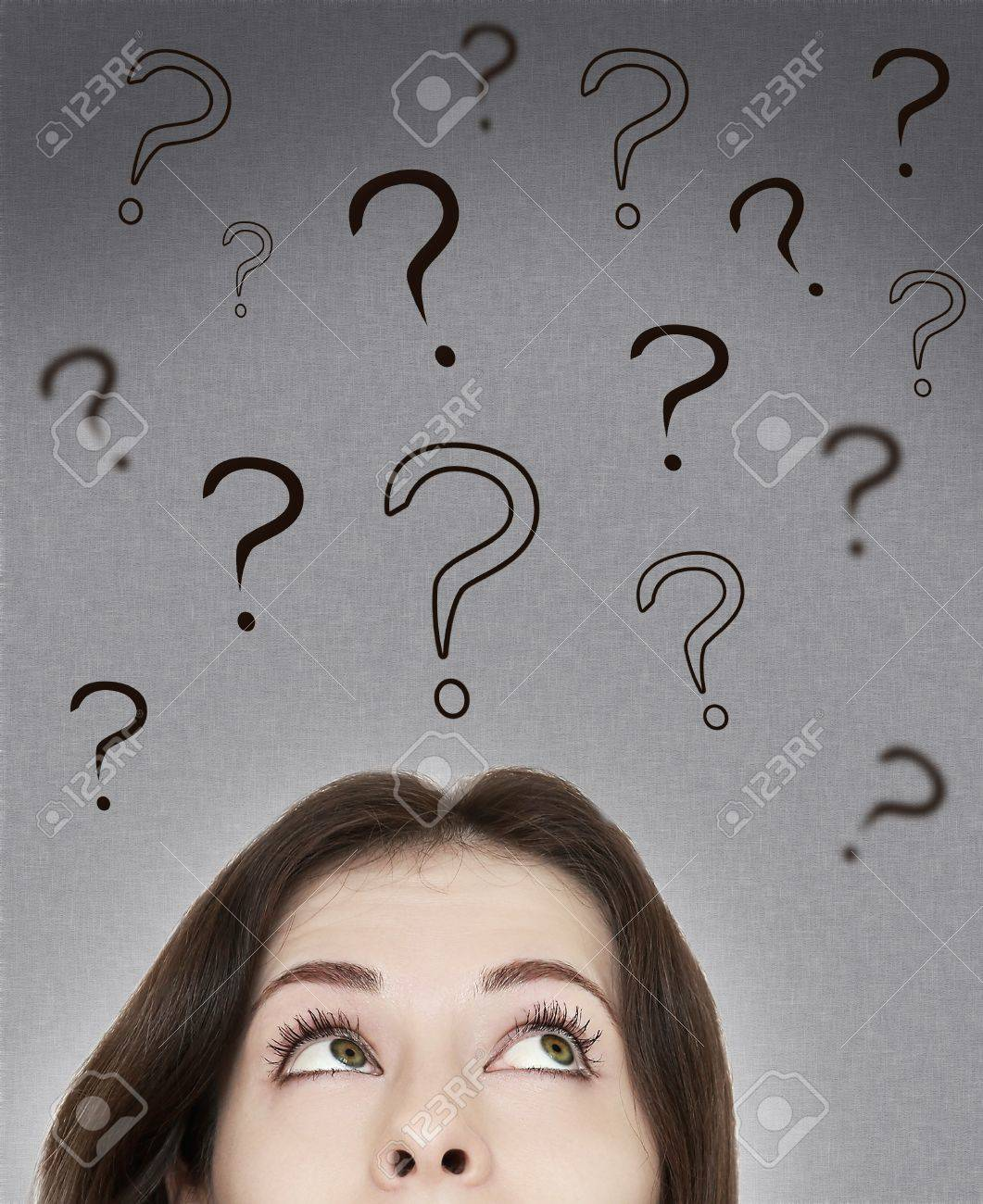 Beautiful thinking woman looking on questions marks above her head on grey background Stock Photo - 18443594