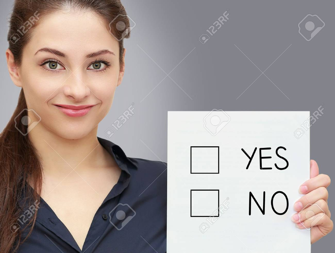 Business woman holding blank with option yes or no on grey background Stock Photo - 19761507