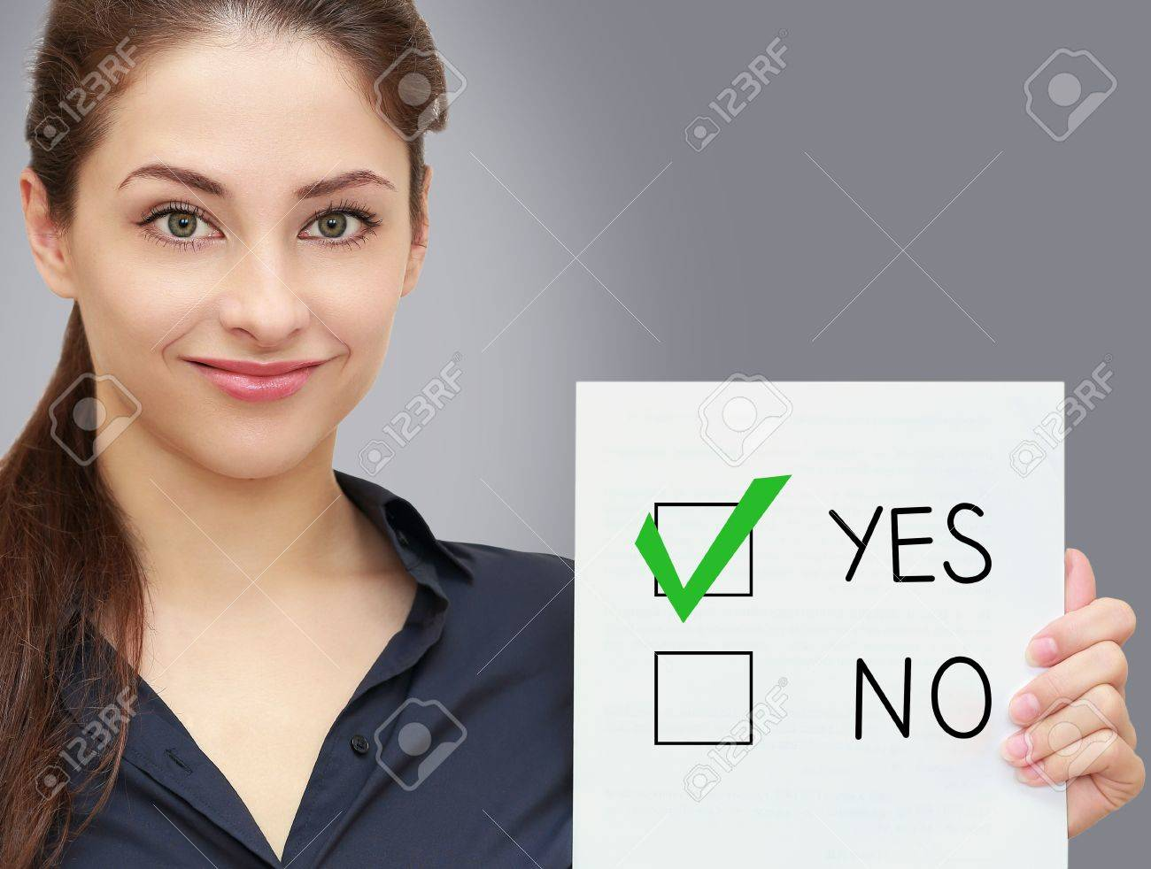 Business woman holding blank and voting for yes in option on grey background Stock Photo - 19761508