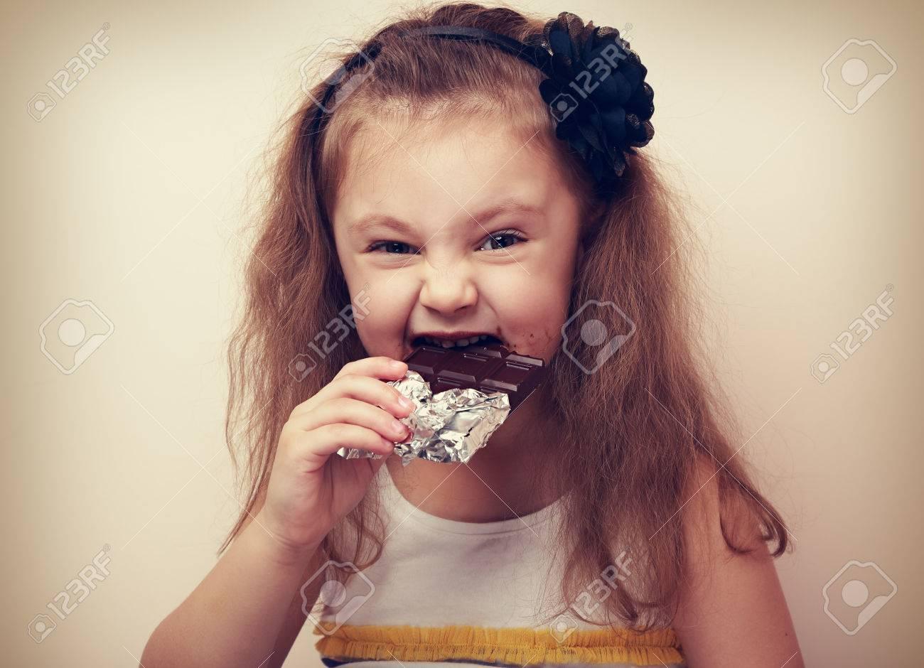 Happy fun smiling kid girl biting dark chocolate with craving eyes. Vintage closeup portrait - 39038546