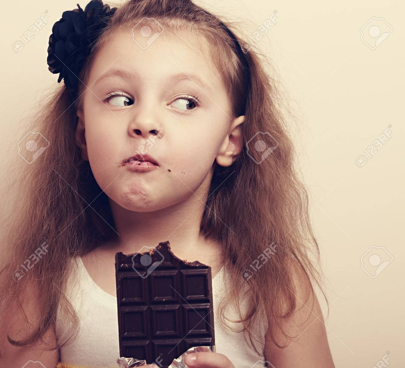 Thinking expression kid girl eating chocolate and looking fun