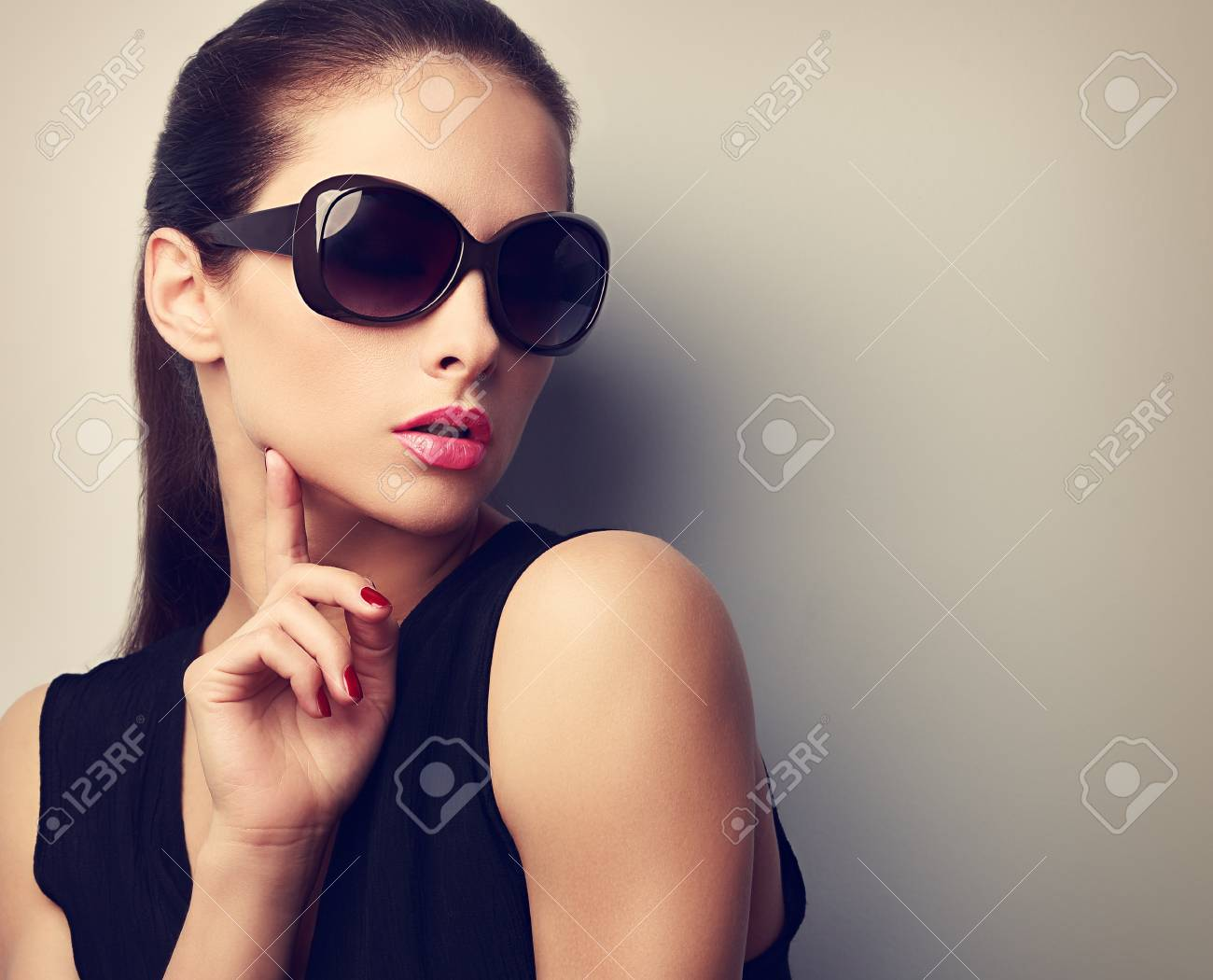 1ee931ffc3d1 Elegant young female model in trendy sunglasses posing touching hand the  face. Vintage closeup portrait