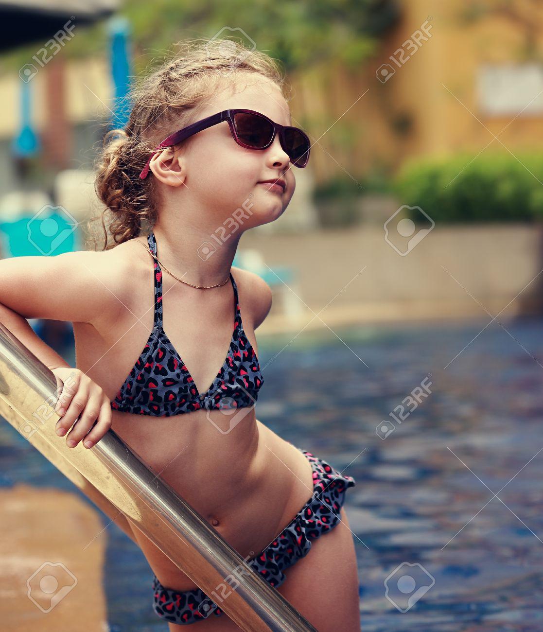 archivio fotografico poco modello femminile in posa in moda per bambini occhiali da sole e costume da bagno vicino alla piscina ritratto del primo piano