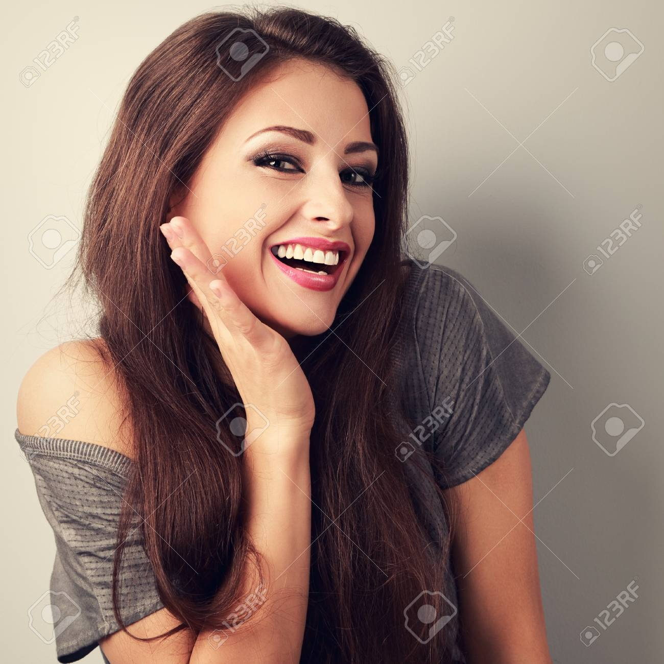 Happy toothy laughing brunette young woman with hand near face. Toned closeup portrait - 57057996