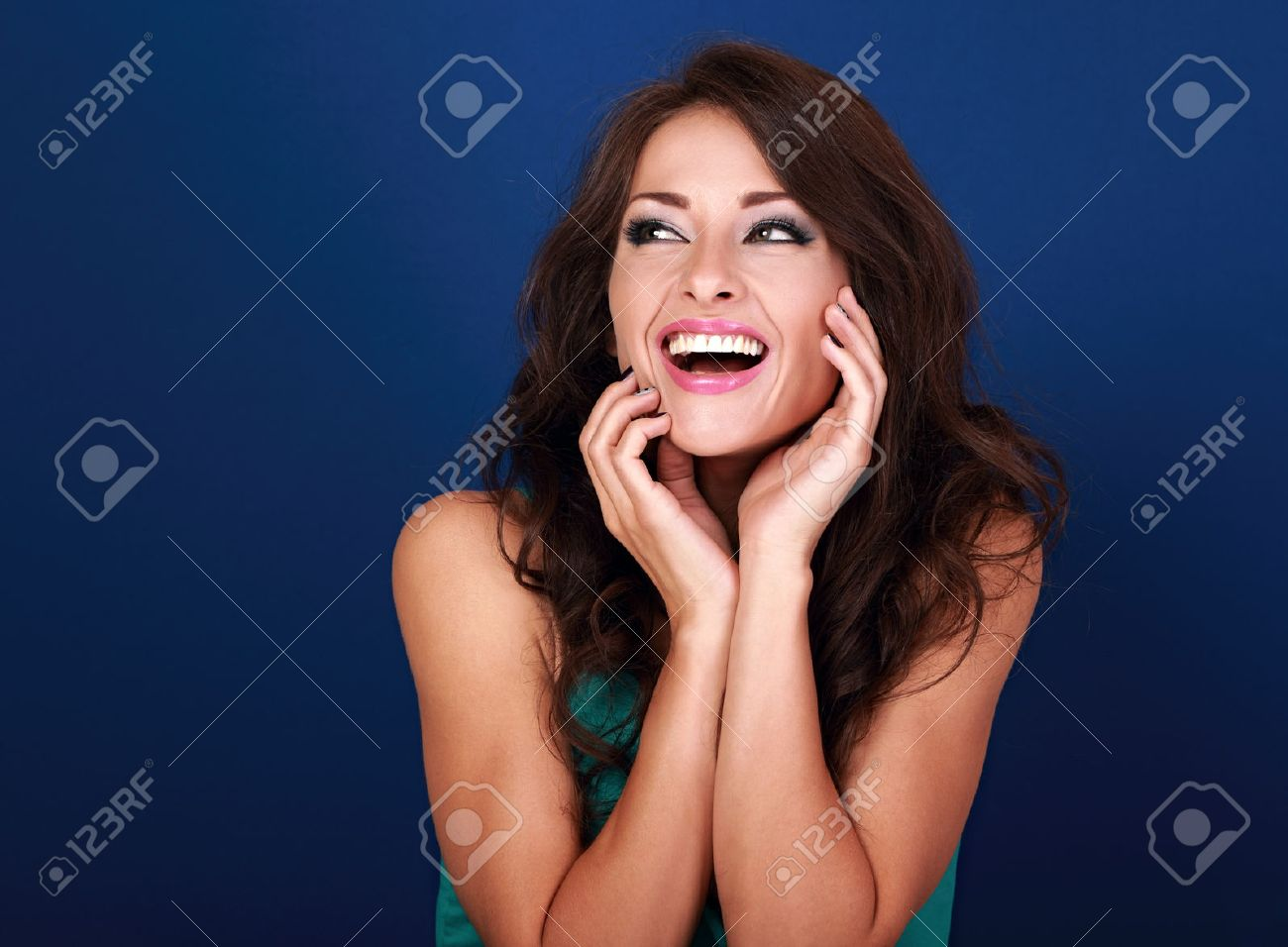 Laughing beautiful curly hair style woman looking with open mouth on bright blue background - 62687319