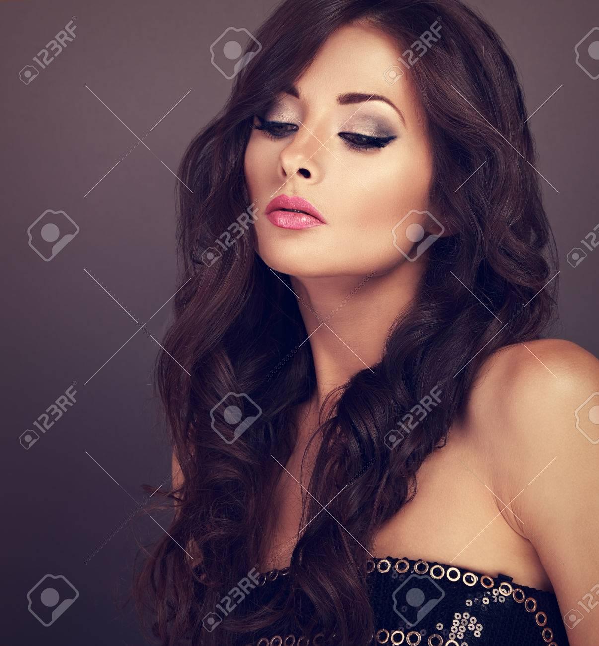 hermosa mujer elegante maquillaje modelo posando con corte de pelo largo y rizado volumen sobre fondo