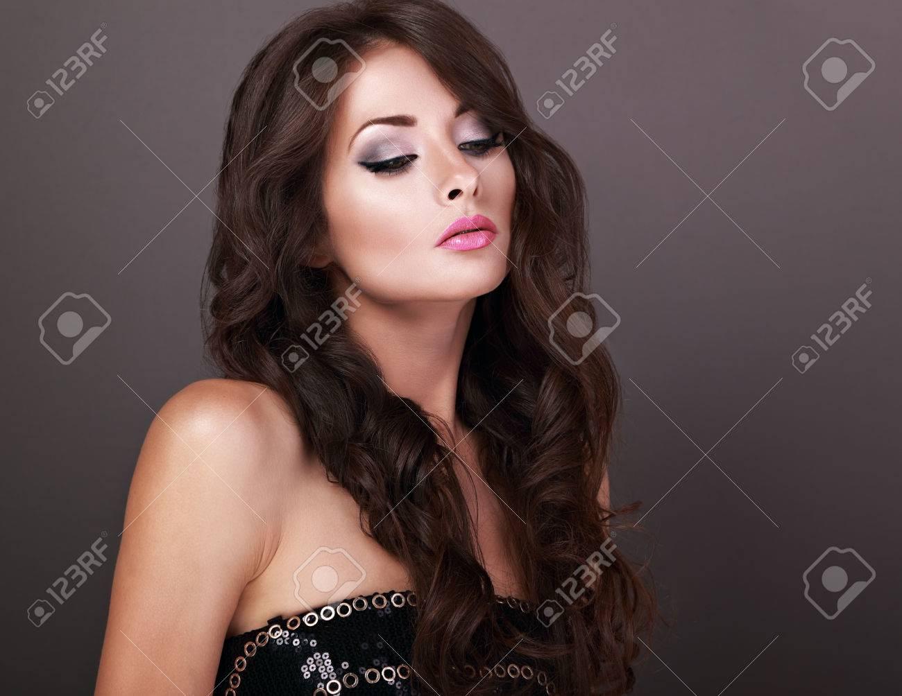 foto de archivo elegante hermosa hembra maquillaje modelo posando con corte de pelo largo y rizado volumen sobre fondo gris
