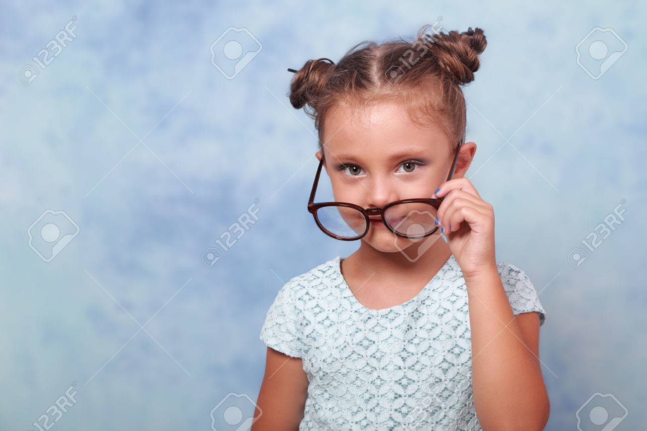 71ae78af35 Stock Photo - Thinking fun kid girl in glasses looking happy and holding  eyeglasses the hand on blue background with empty copy space.