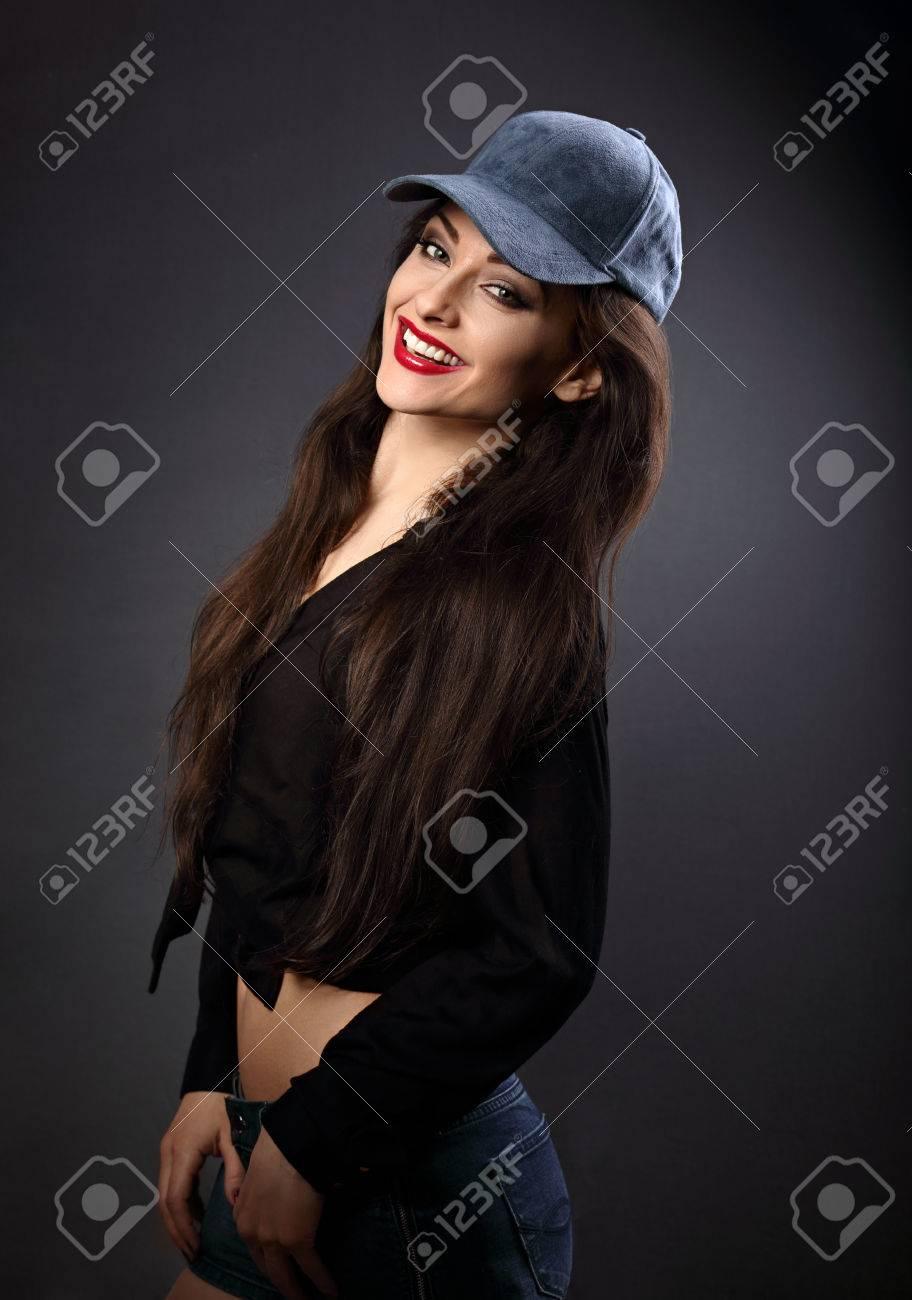 729edbef4bca Feliz sonriente mujer morena hermosa en gorra de béisbol azul con estilo de  pelo largo en la moda camisa negra que mira en el fondo oscuro de la ...