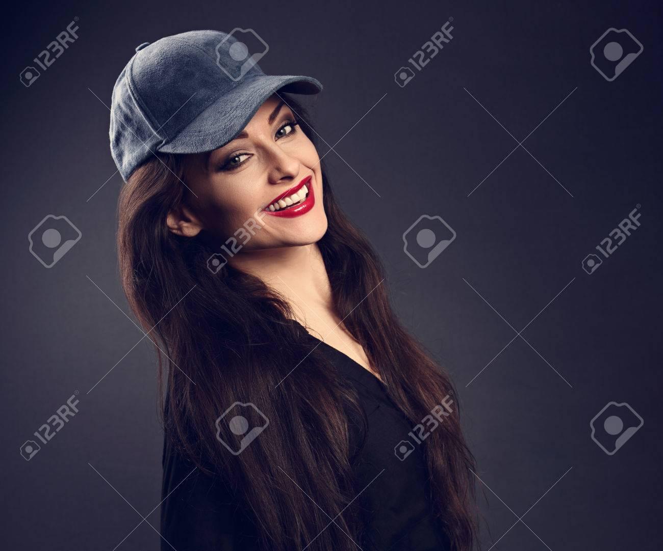 674bd312f5a1 Feliz toothy sonriente mujer morena hermosa en gorra de béisbol azul con  estilo de pelo largo en la moda camisa negra mirando en el fondo de sombra  ...