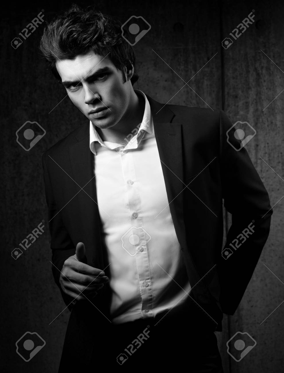 Sexy handsome male model posing in black fashion suit and white style shirt on dark shadow