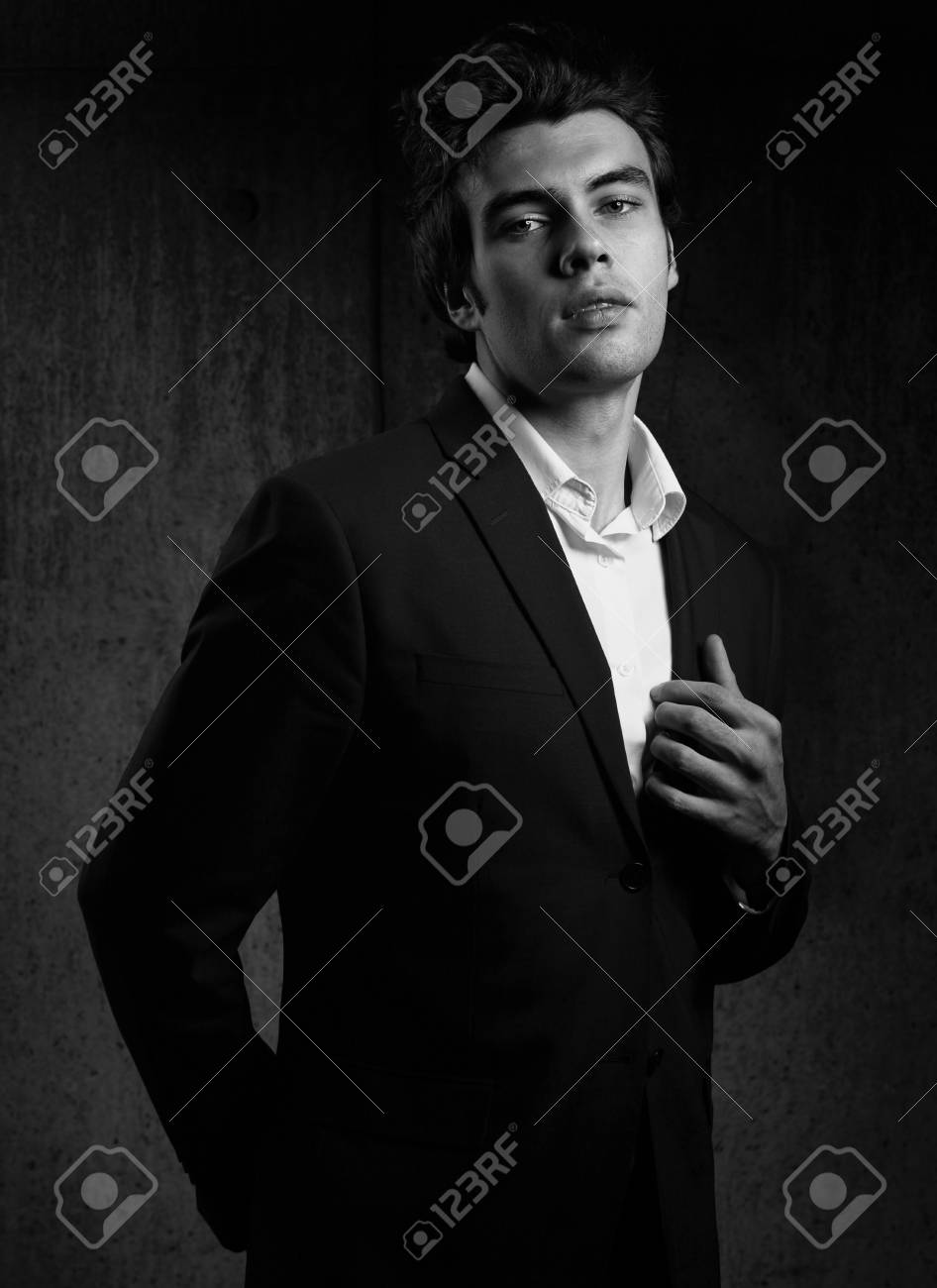 Handsome male model posing in fashion suit and white style shirt looking on dark shadow background