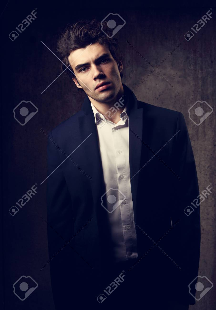 4bffa67d Handsome male model posing in fashion suit and white style shirt looking on dark  shadow background