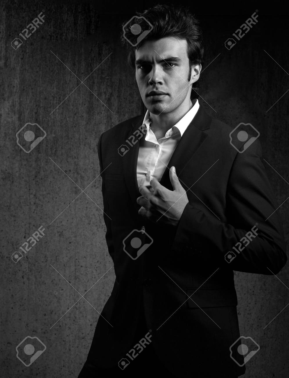 a8f02bd1 Charismatic handsome male model posing in fashion suit and white style  shirt looking on dark shadow