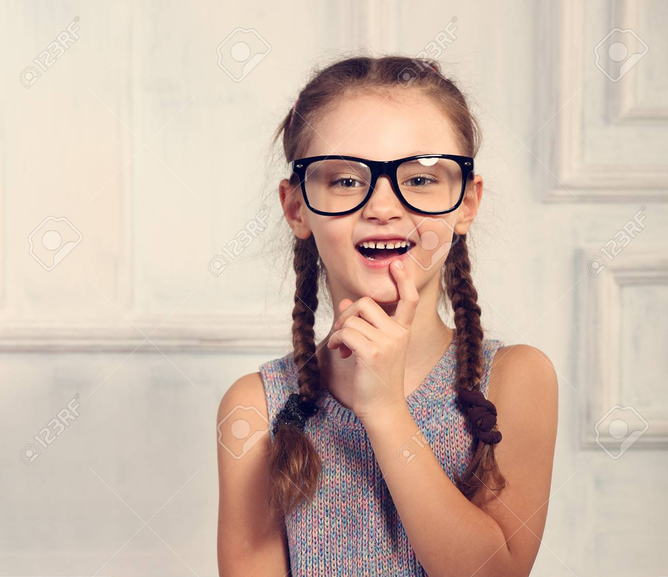 a1f30976eb Excited positive thinking kid girl in fashion glasses with emotional  natural smiling face looking on studio