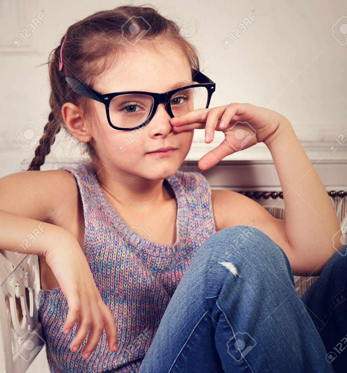 57bfc2d22 Serious emotional calm kid girl in eyeglasses looking and thinking about  life problem in blue jeans