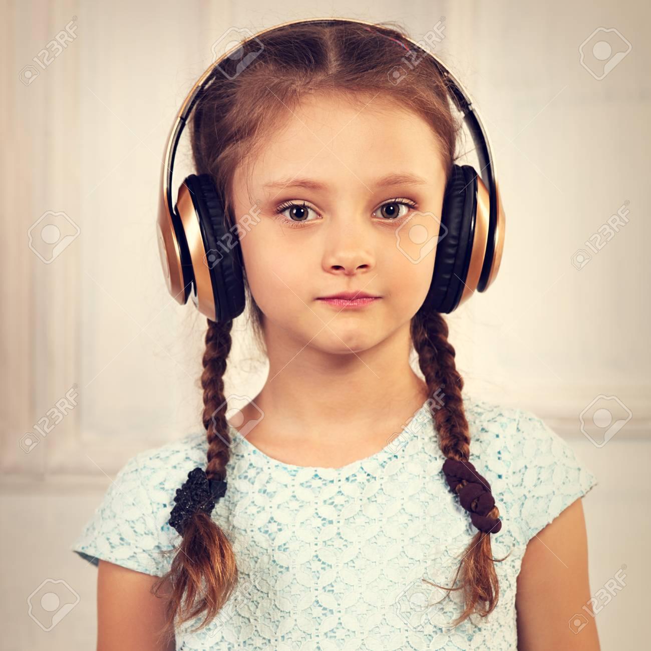 54255f039 Foto de archivo - Muchacha seria tranquila feliz del niño en vestido azul  que escucha la música en auriculares inalámbricos en fondo del estudio.