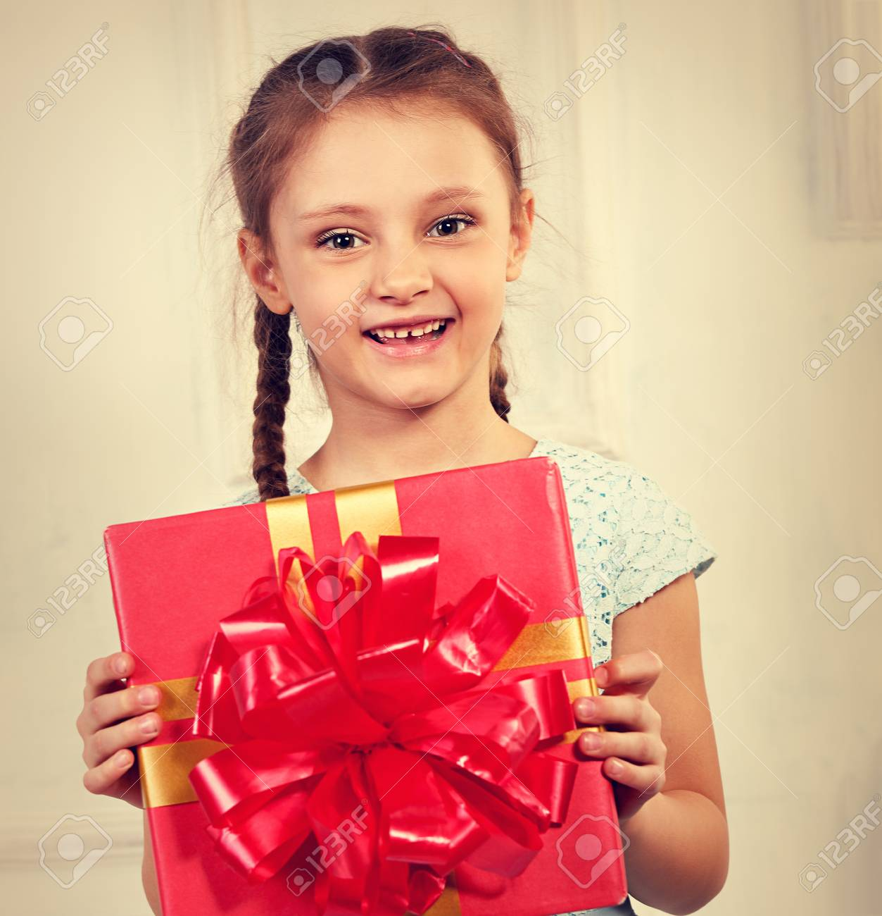 08fe10492de Beautiful cute kid girl holding present box with red ribbon bow and looking  happy on it