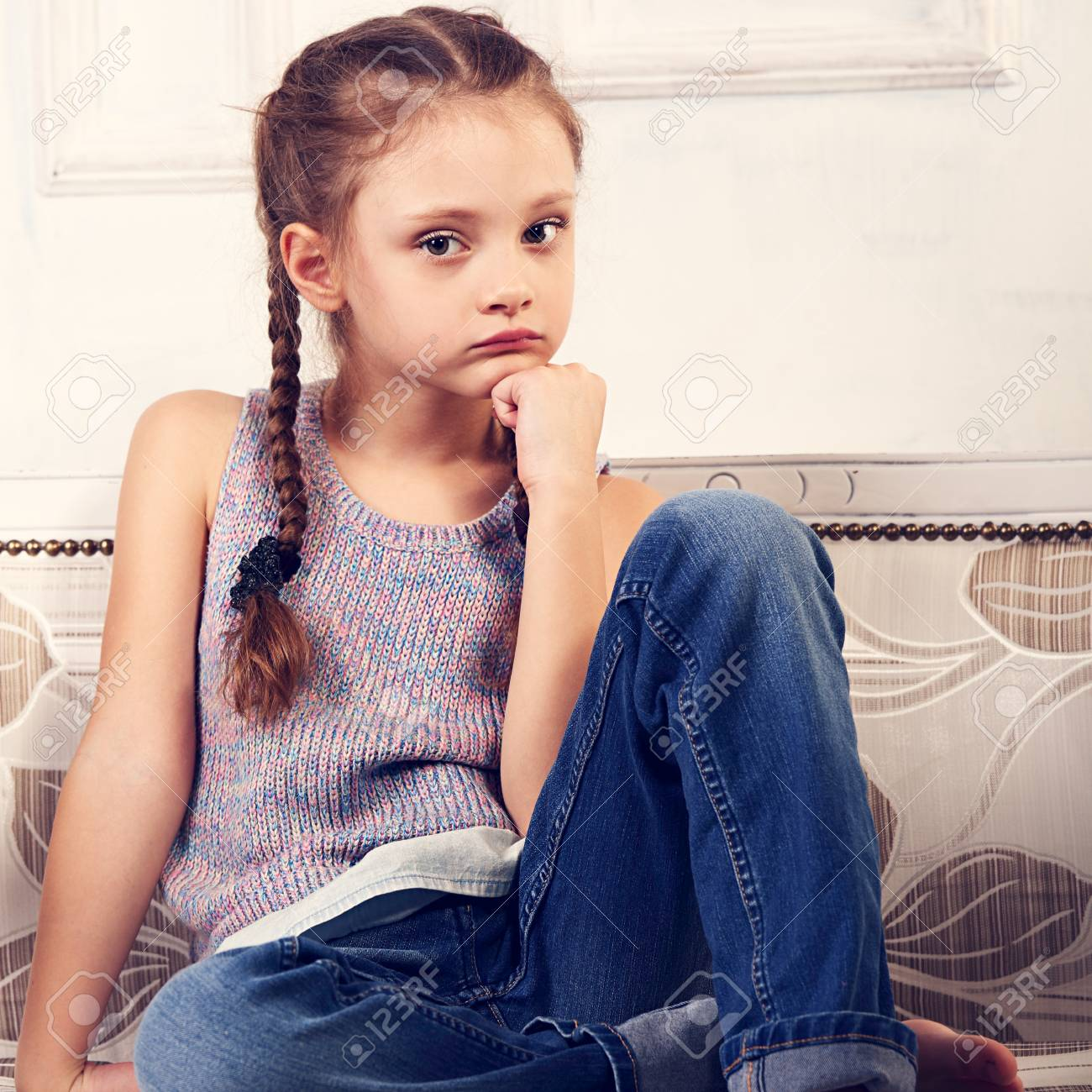 78e37e830 Beautiful calm thinking unhappy kid girl sitting on the bench in blue jeans  and fashion blouse