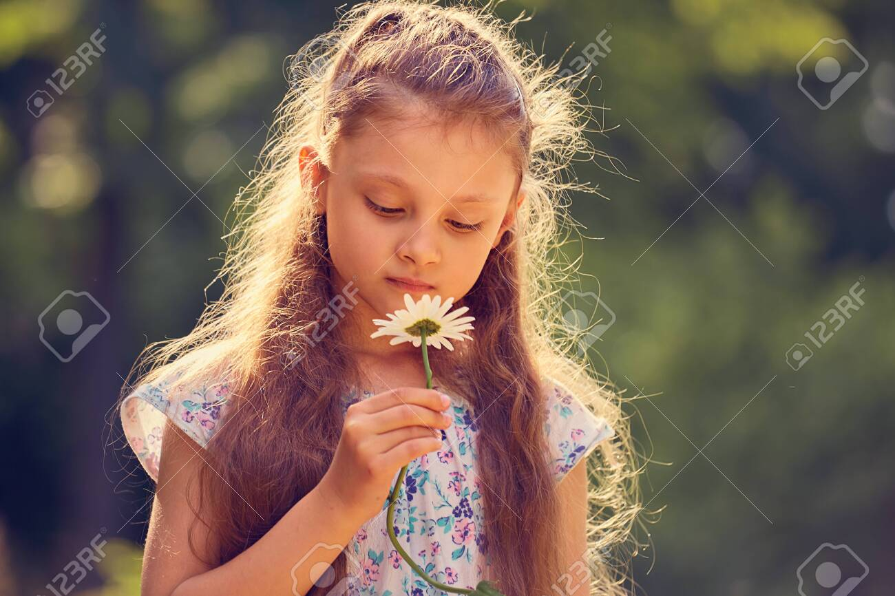 Beautiful kid girl looking on chamomile flower on nature summer green background. Closeup bright portrait - 121118637
