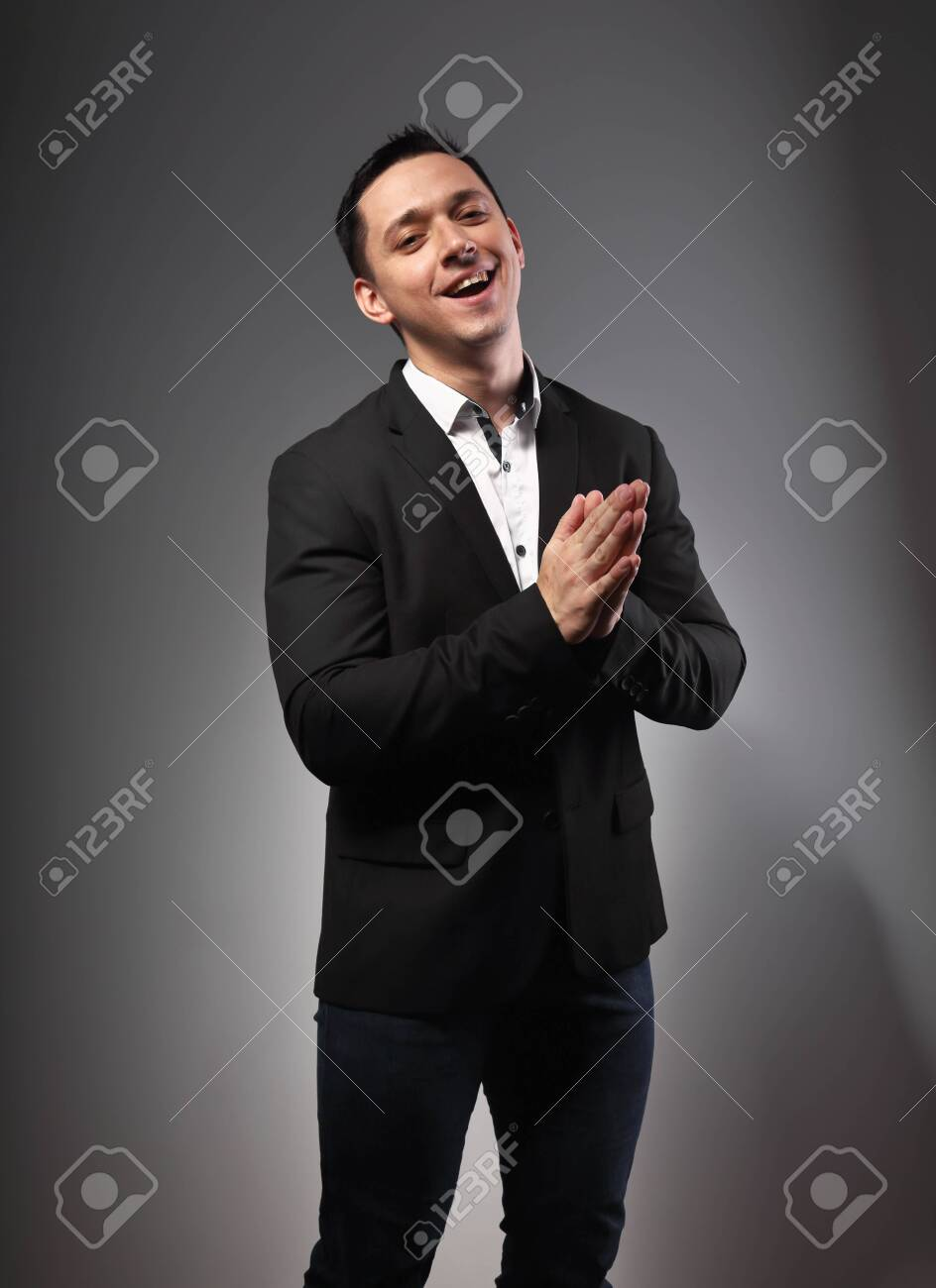 Happy smiling full energy excited young business man in black suit clapping in the palms on grey dark background with empty copy space. Closeup portrait - 135166485