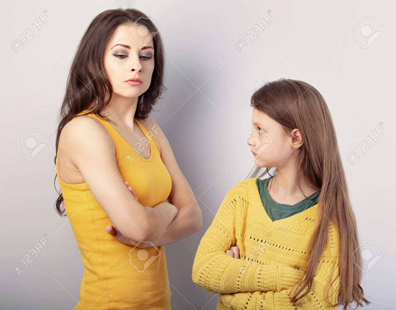 Beautiful concentrated strict mother and her serious emotional thinking daughter looking each other on blue background. Concept family emotion portrait. - 165435461