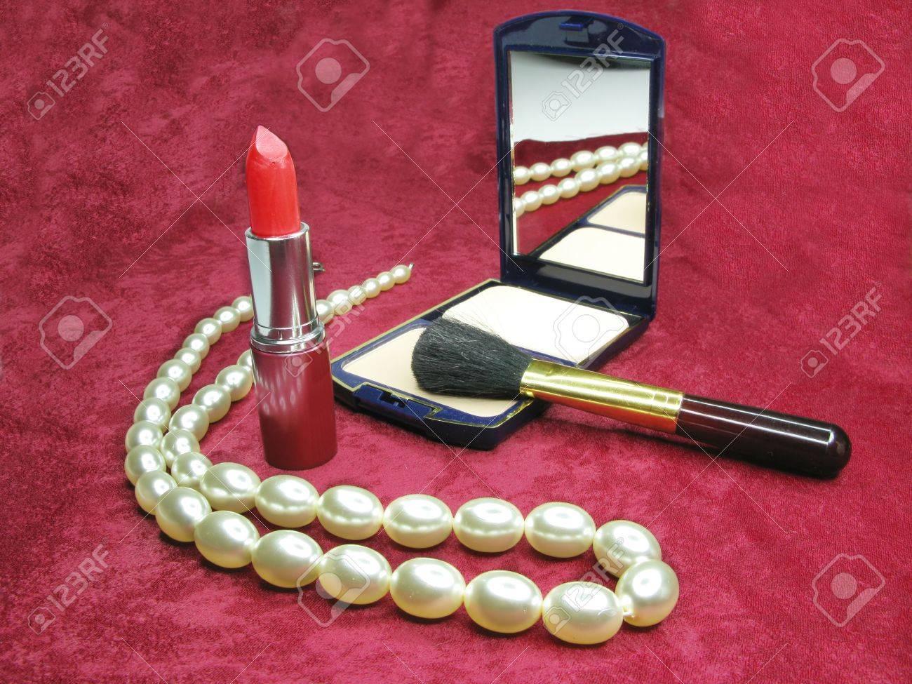 red lipstick powder white beads on purple cloth background Stock Photo - 11921232