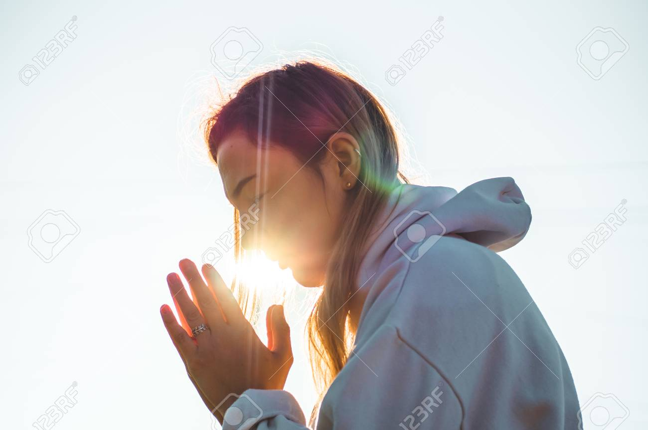In the morning Girl closed her eyes, praying outdoors, Hands