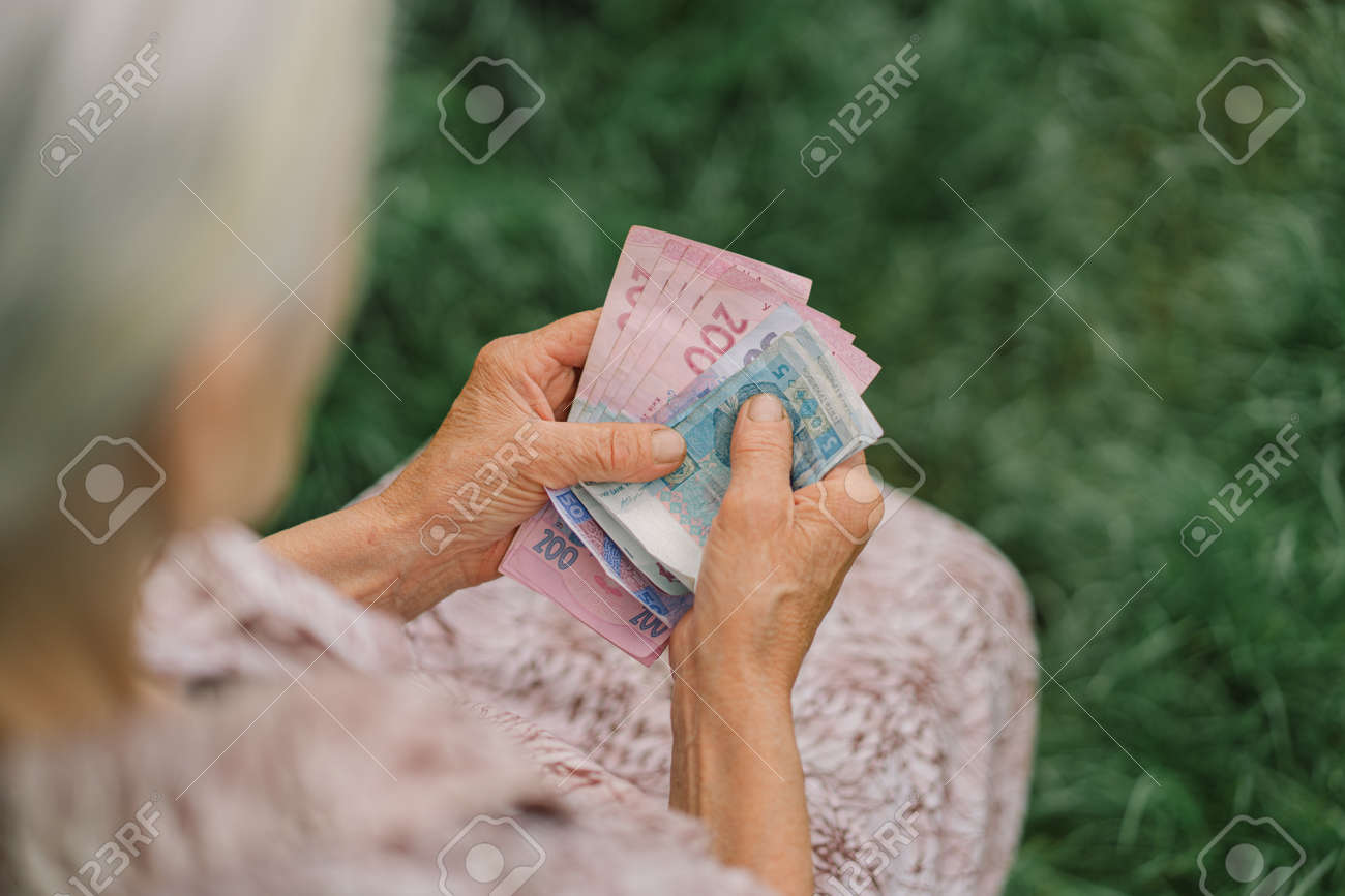 Concerned elderly woman counting Ukrainian money hryvnia. The concept of old age, poverty, austerity. - 171412543