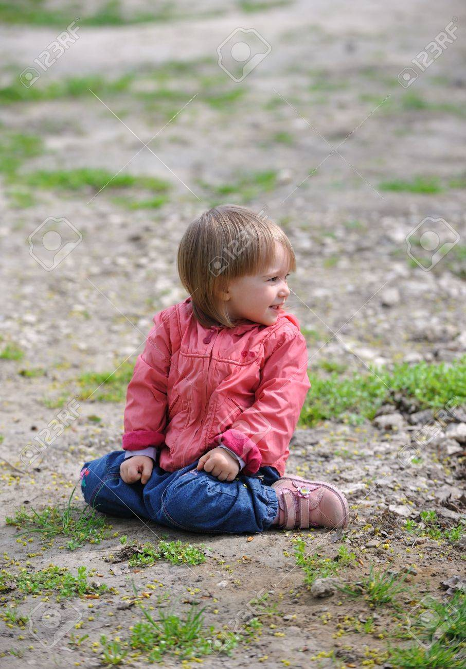 little girl sit ground Little girl sitting on ground smiling looking to side.