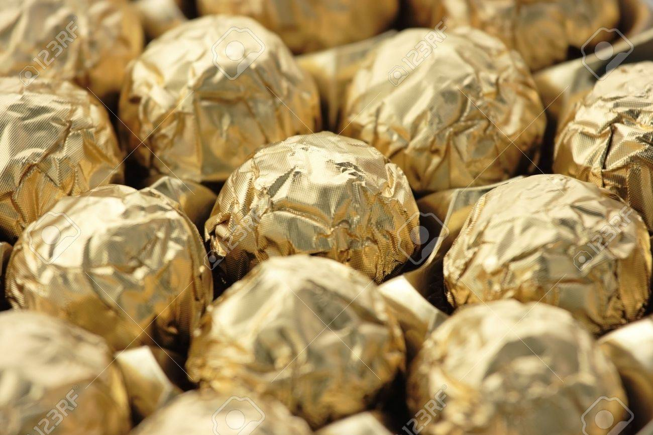 Chocolate Sweets In Golden Foil. Focus On A Central Ball, Shallow ...