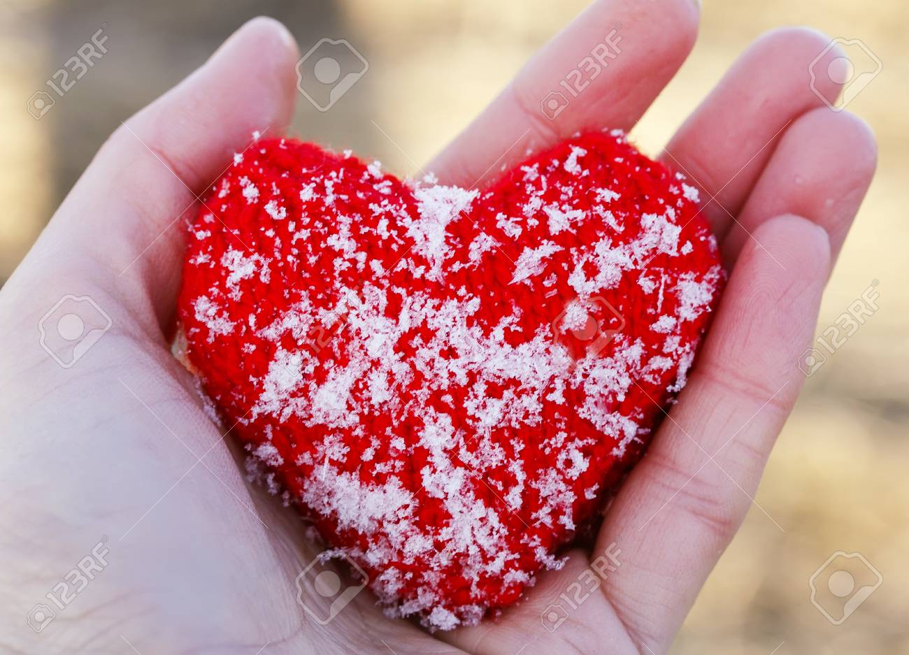 Stock photo warm knitted red heart is covered with cold ice crystals lies in the palm of your hand