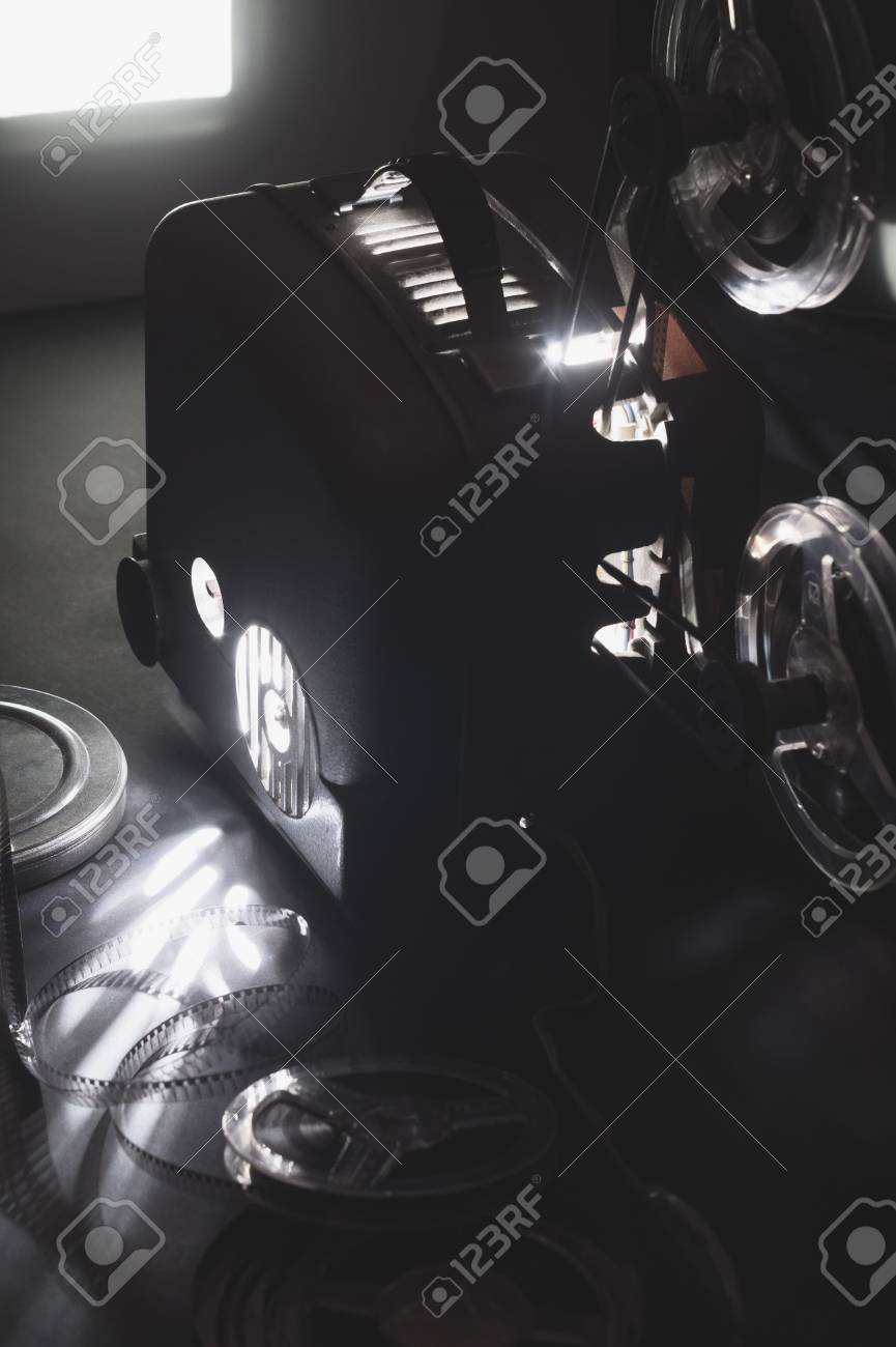 Old Cinema Projector And The Glowing Screen In Dark Stock Photo