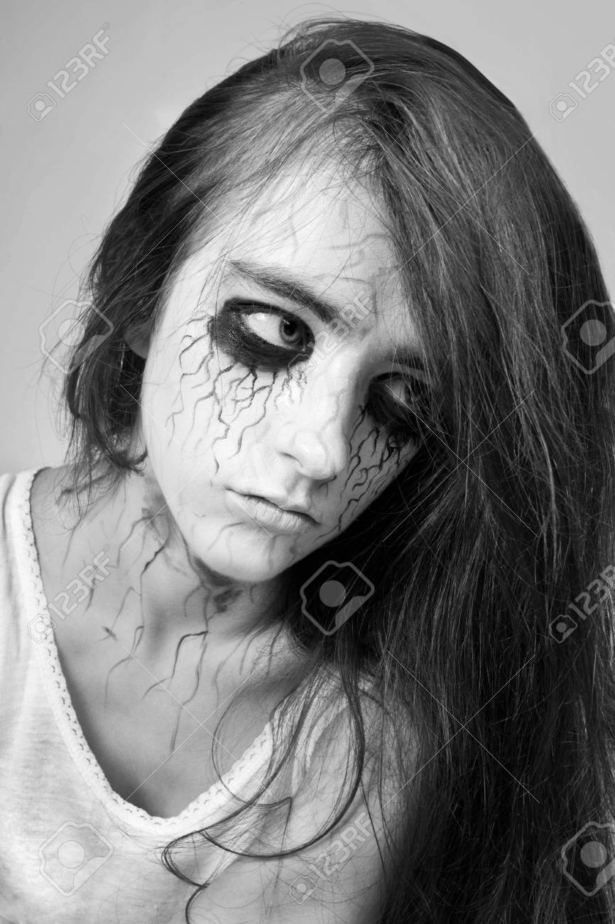 Portrait sad girl zombie with black veins on her face concept of halloween