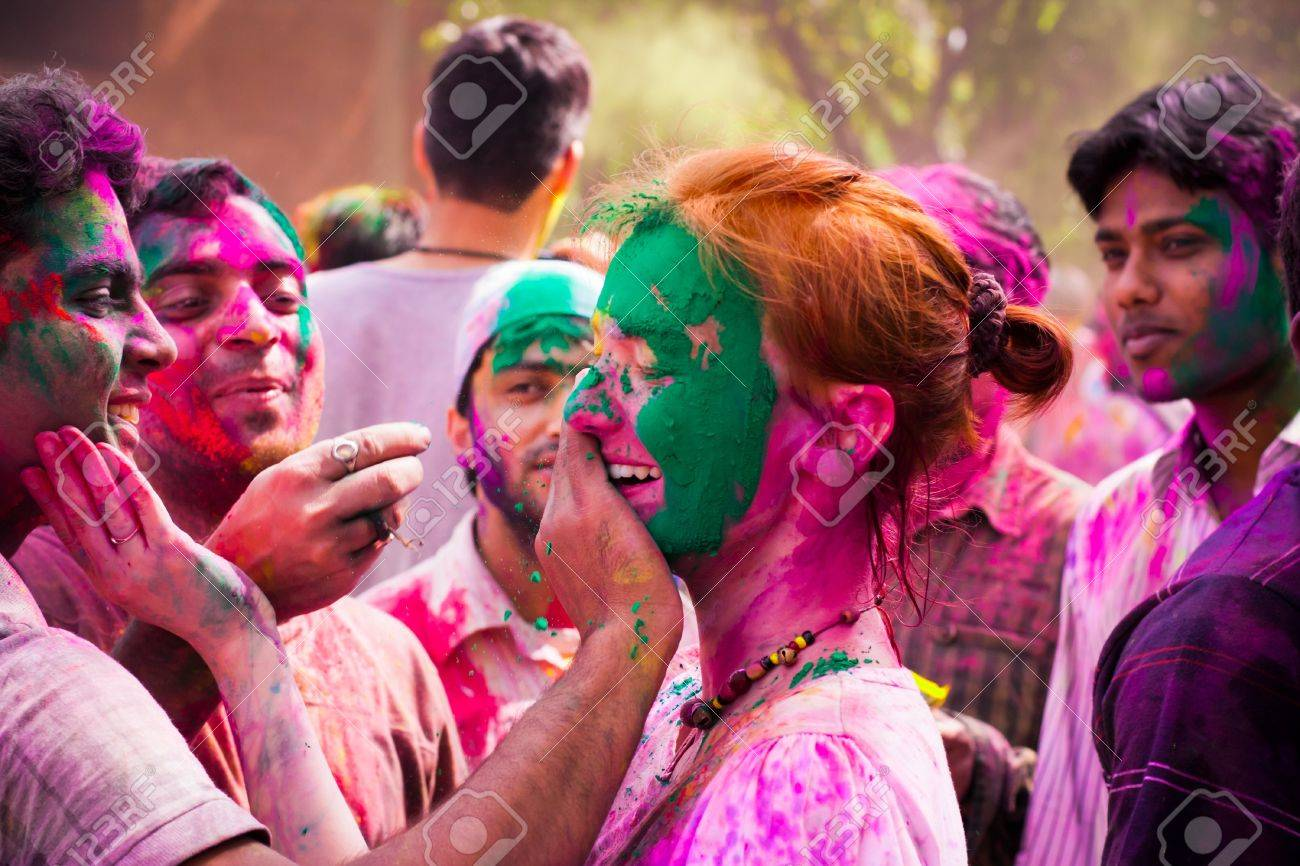 Woman tourist celebrating the Indian festival of Holi with the local Indian population People at the holi festival in India Holi, or Holli,is a spring festival celebrated by Hindus, Sikhs and others The main day, Holi, is celebrated by people throwing - 20976495