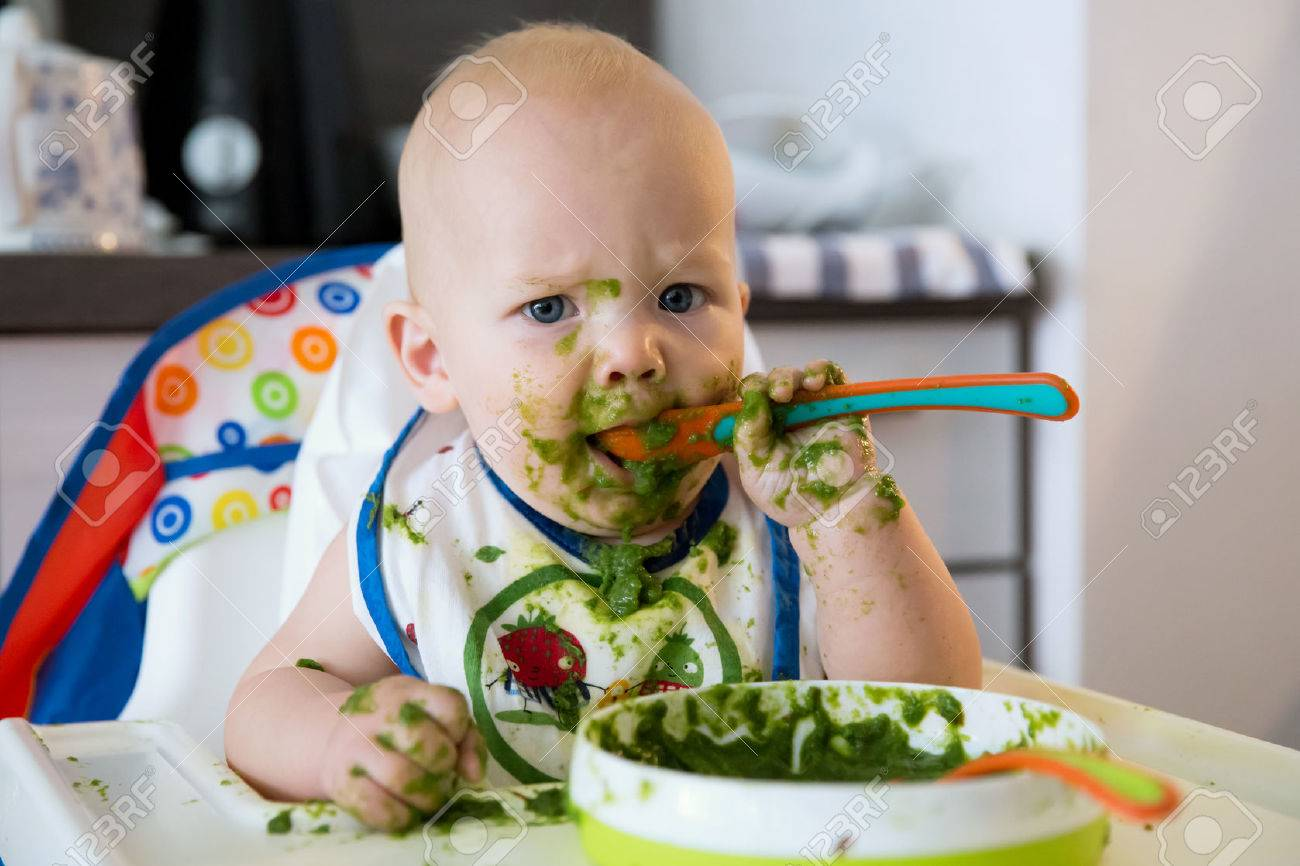 feeding. adorable baby child eating with a spoon in high chair