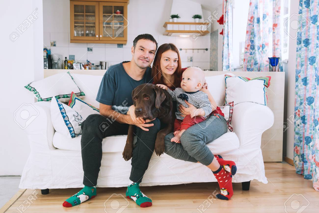 Happy Parents With Baby And Dog On The Couch At Home Interior Lifestyle Family