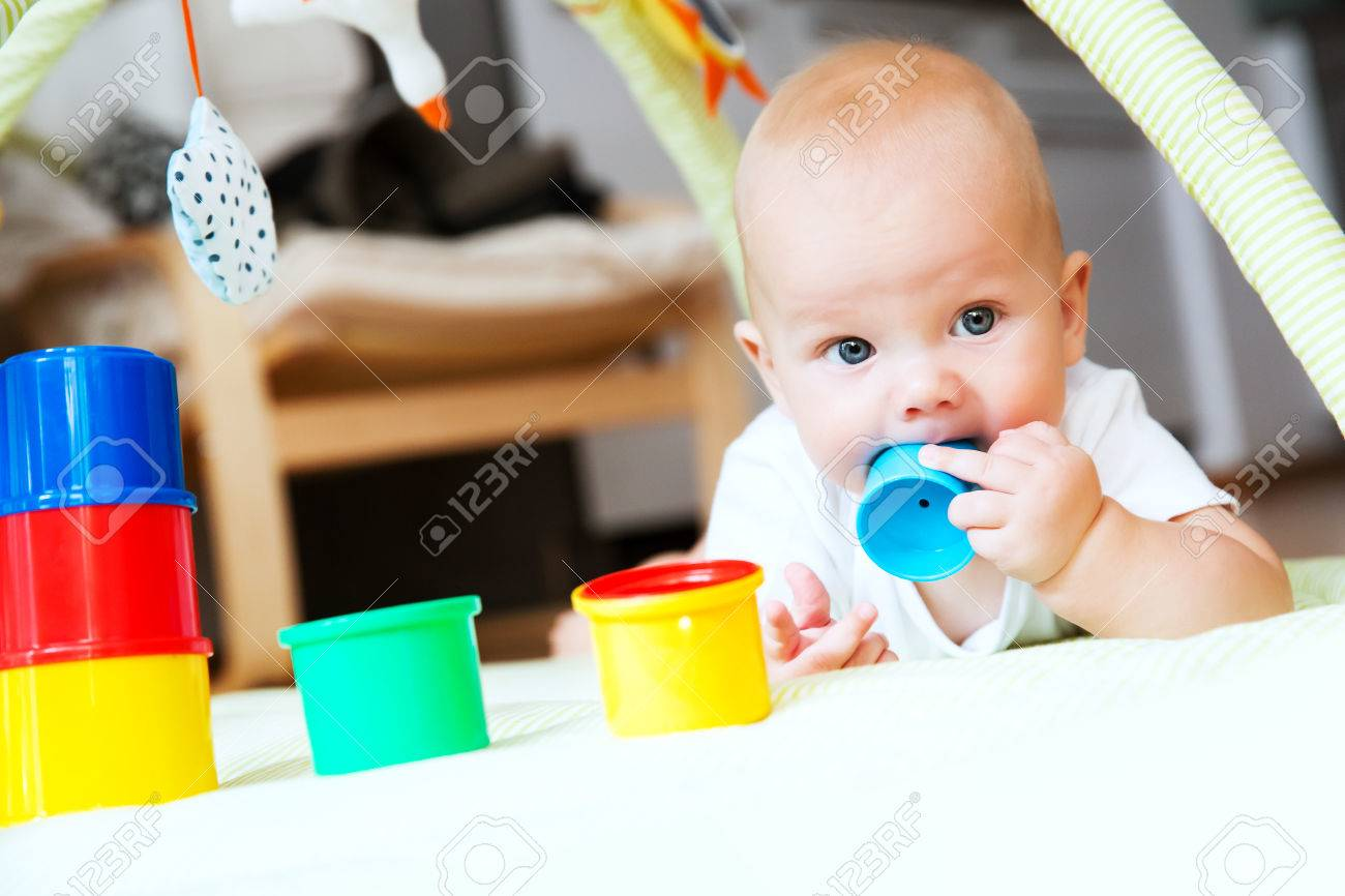 Baby Playing With Colorful Toys At Home Happy 6 Months Old Baby