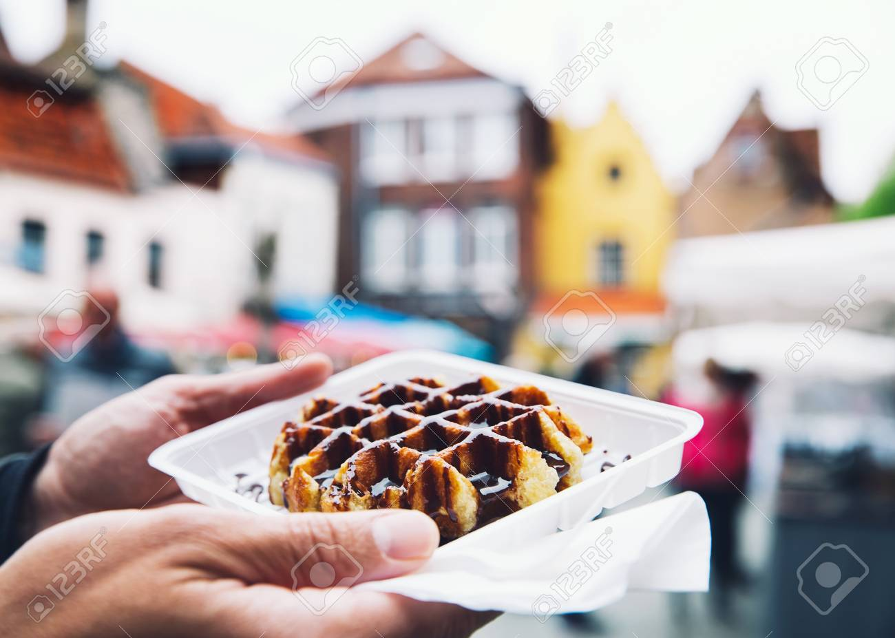 Tourist holds in hand popular street food - Belgium tasty waffle with chocolate sauce on the background of city tourist streets of Bruges, Belgium, Europe. Traditional Belgian dessert, pastry. - 78568661
