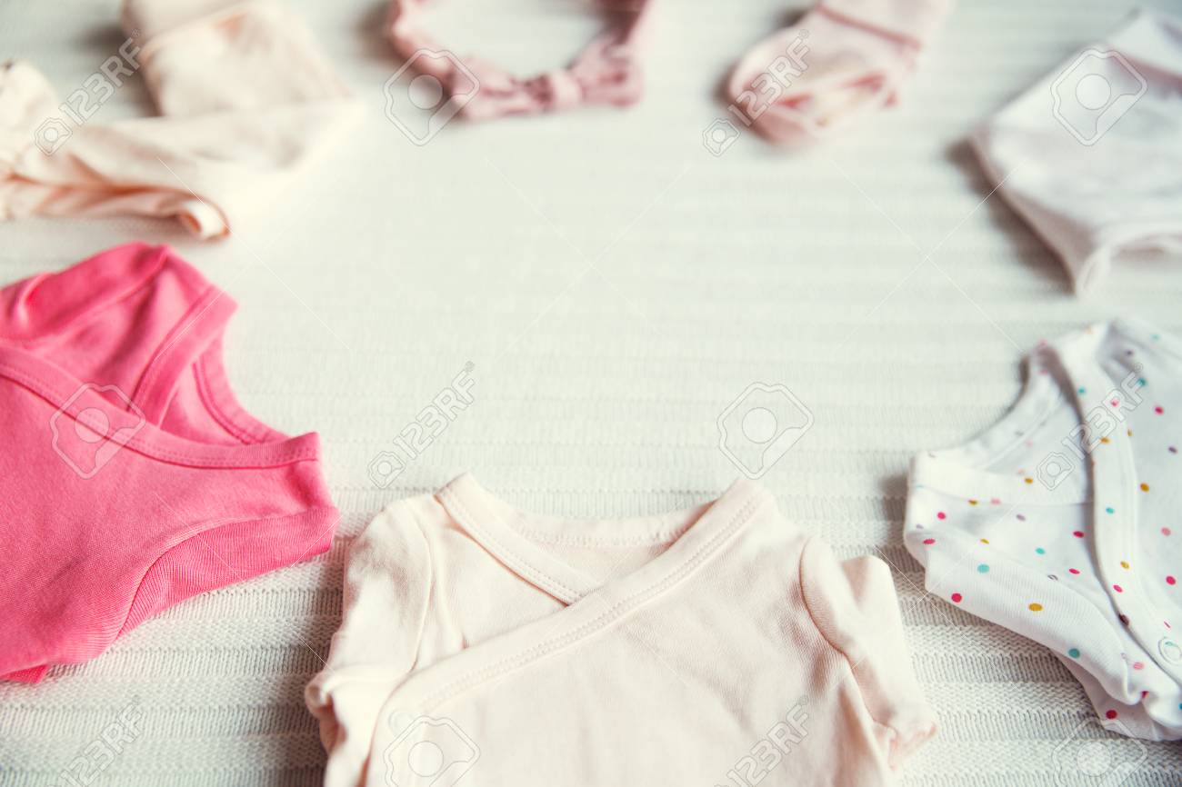 400d53658 Baby clothes on light pastel fabric background. Gentle, soft and cozy mood.  Newborn