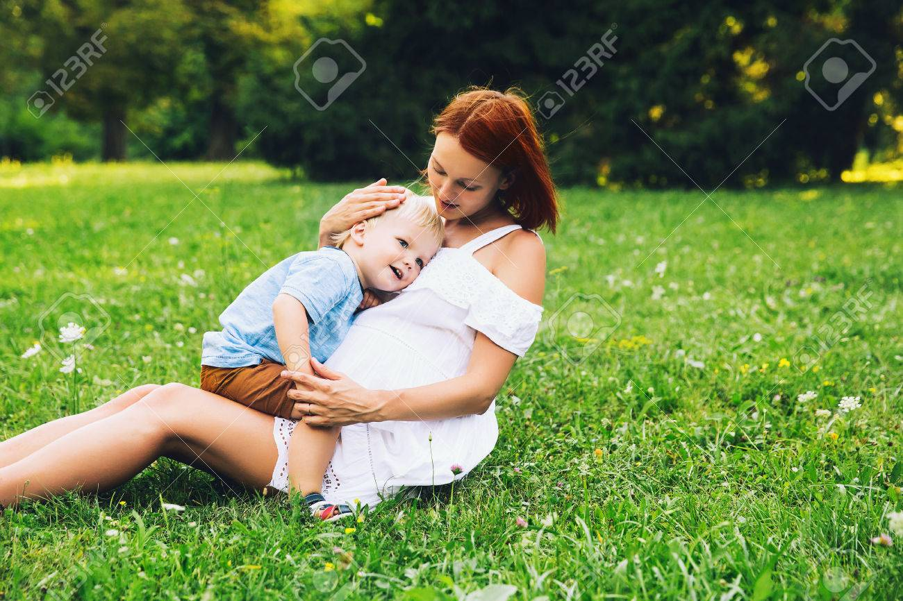 Pregnant woman with toddler kid outdoors. Mother and her son on nature in summer park. Little child boy hugging mother, who pregnant for second time. Pregnancy, new life, family, birth concept. - 83755628