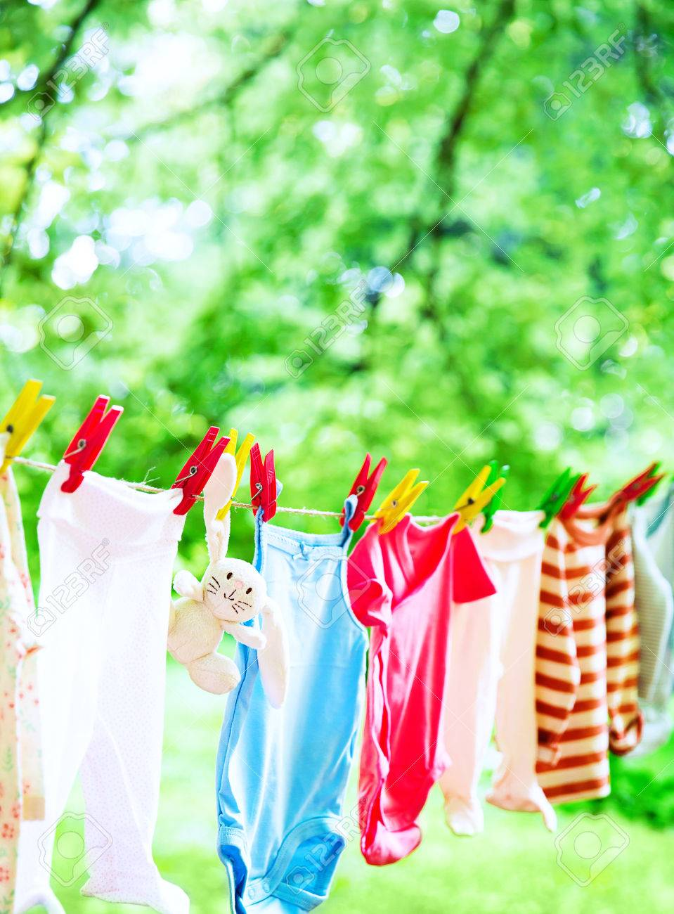Baby cute clothes hanging on the clothesline outdoor. Child laundry hanging on line in garden on green background. Baby accessories. - 85254827