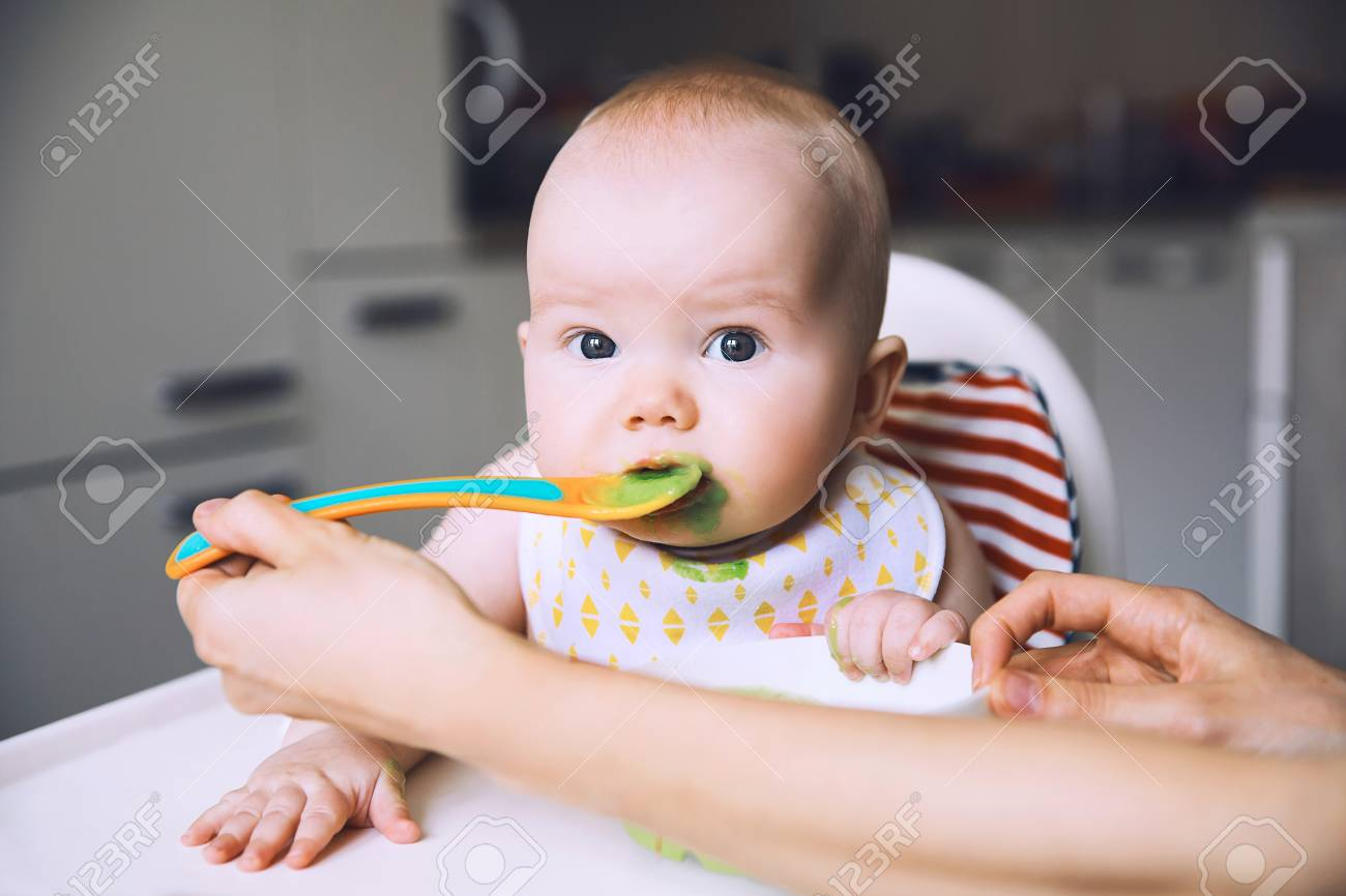 Feeding. Messy smiling baby eating with a spoon in high chair. Baby's first solid food. Mother feeding little child with spoon of puree. Daily routine. Finger food. Healthy child nutrition. - 101131597