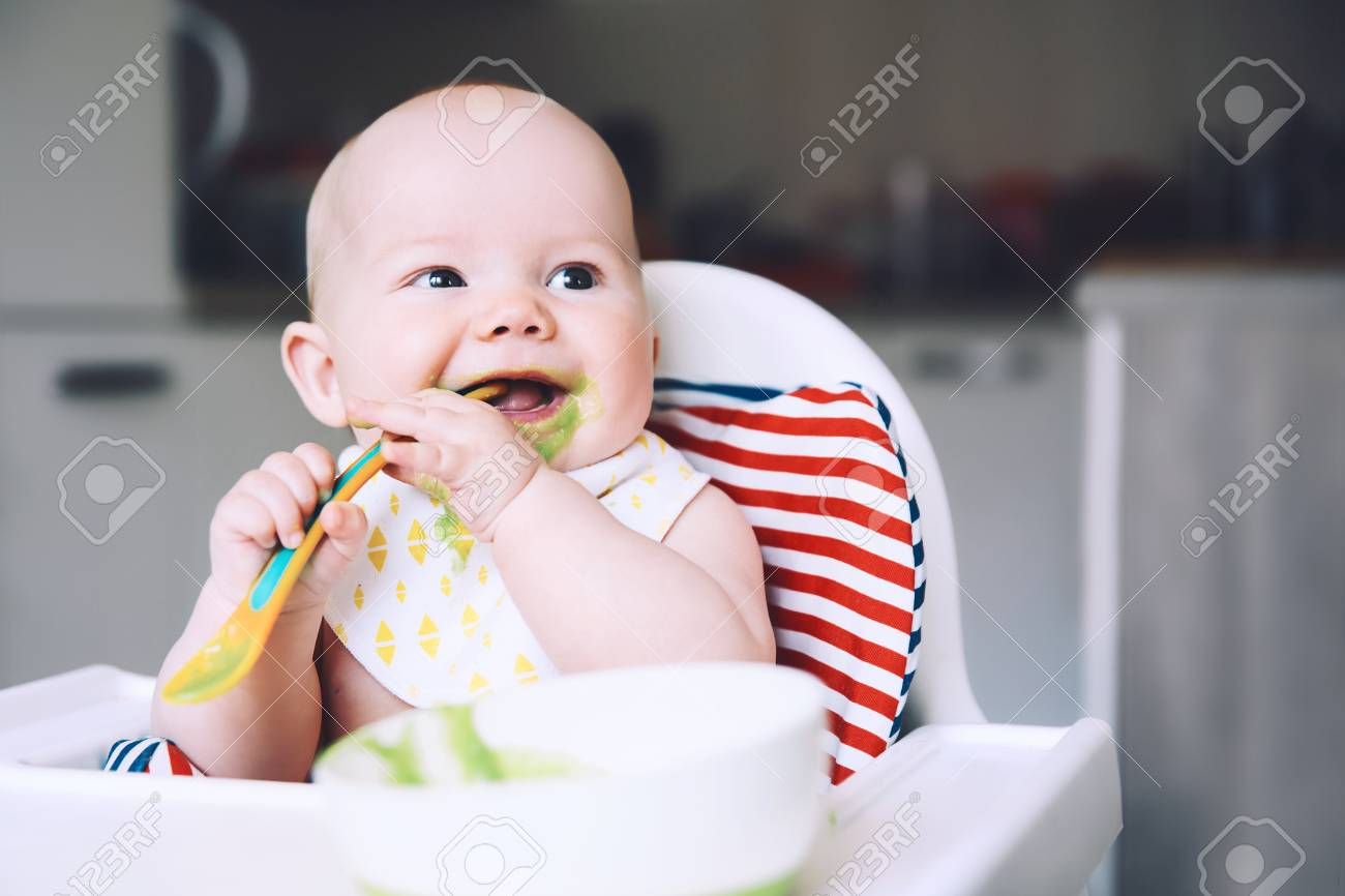 Feeding. Messy smiling baby eating with a spoon in high chair. Baby's first solid food. Mother feeding little child with spoon of puree. Daily routine. Finger food. Healthy child nutrition. - 101074329